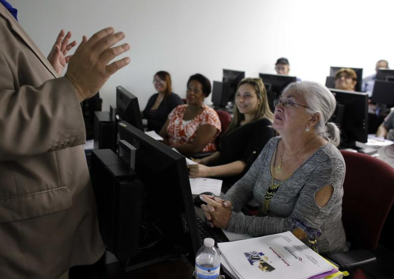 In this Thursday, Feb. 6, 2014, photo, Rosi Pozzi, 73, of Davie, Fla., right, listens during a job search workshop at WorkForce One, in Davie, Fla. Two straight weak job reports have raised doubts about economists' predictions of breakout growth in 2014. The global economy is showing signs of slowing again. (AP Photo/Lynne Sladky)