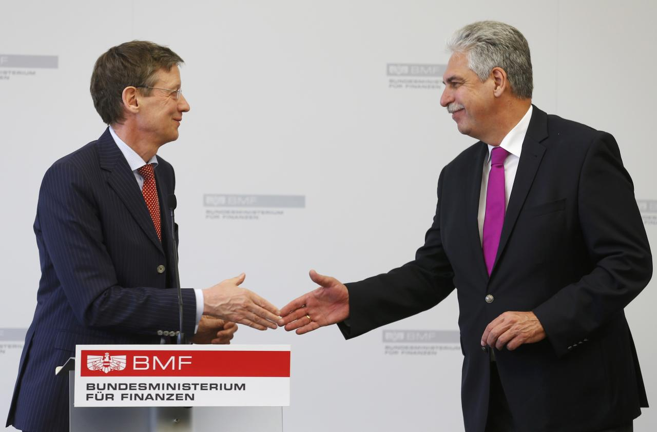 Austria's Finance Minister Hans Joerg Schelling (R) and spokesman for the umbrella group of Heta creditors Friedrich Munsberg shake hands after a news conference in Vienna, Austria, May 18, 2016. REUTERS/Heinz-Peter Bader