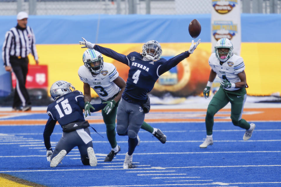 Nevada defensive back EJ Muhammad (4) reaches for the ball after it was tipped in to the air on a pass by Tulane during the first half of the Idaho Potato Bowl NCAA college football game, Tuesday, Dec. 22, 2020, in Boise, Idaho. Nevada intercepted the ball on the play. (AP Photo/Steve Conner)