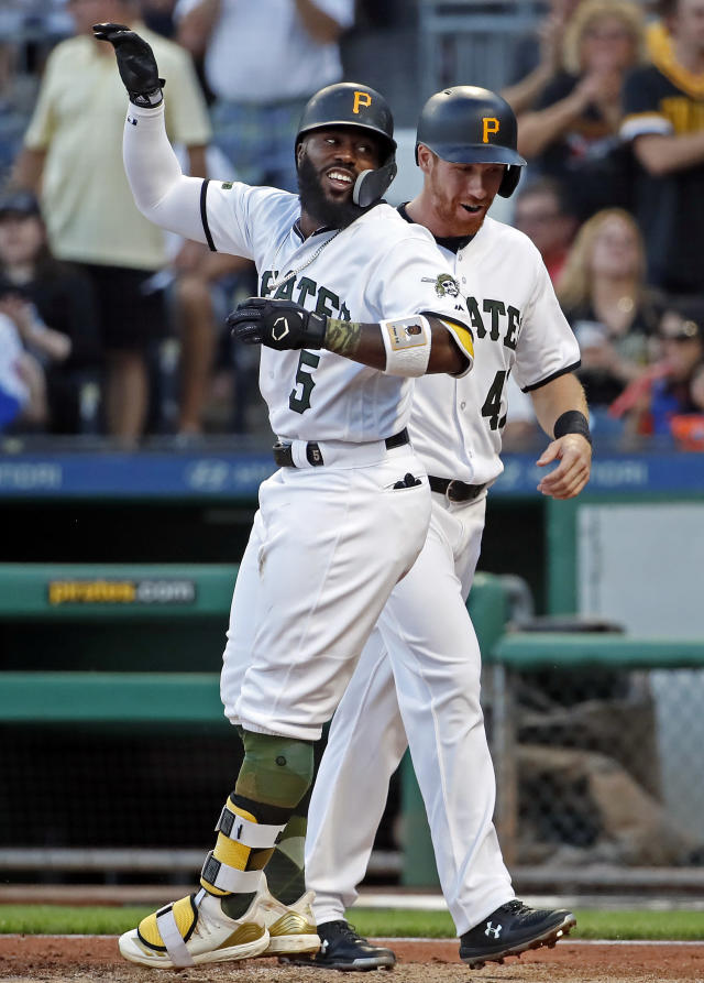 Pittsburgh Pirates' Josh Harrison, left, celebrates with Jordan Luplow as he crosses home plate after hitting a two-run home run off New York Mets starting pitcher Steven Matz during the third inning of a baseball game in Pittsburgh, Thursday, July 26, 2018. (AP Photo/Gene J. Puskar)