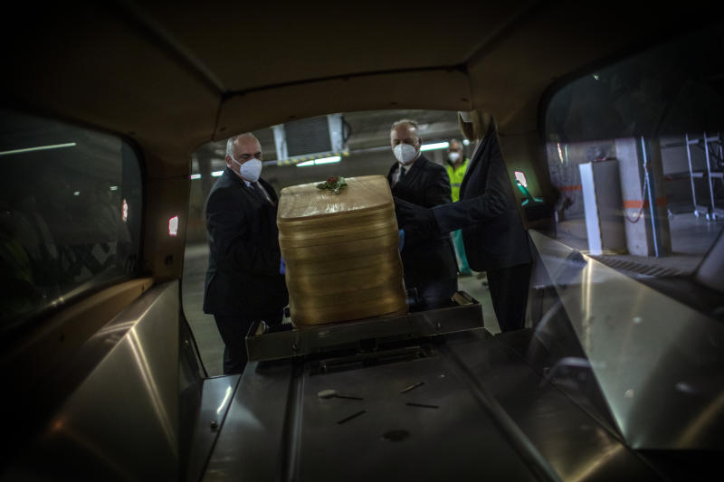 Mortuary service workers load inside a hearse the coffin of the last COVID-19 victim stored at an underground parking garage that was turned into a morgue, at the Collserola funeral home in Barcelona, Spain. May 17, 2020. A funeral home in Barcelona has closed a temporary morgue it had set up inside its parking garage to keep the victims of the Spanish city's coronavirus outbreak. The last coffin was removed and buried on Sunday. In 53 days of use, the temporary morgue has held more than 3,200 bodies. (AP Photo/Emilio Morenatti)