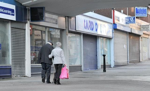 People walking past closed shops (Martin Rickett/PA)