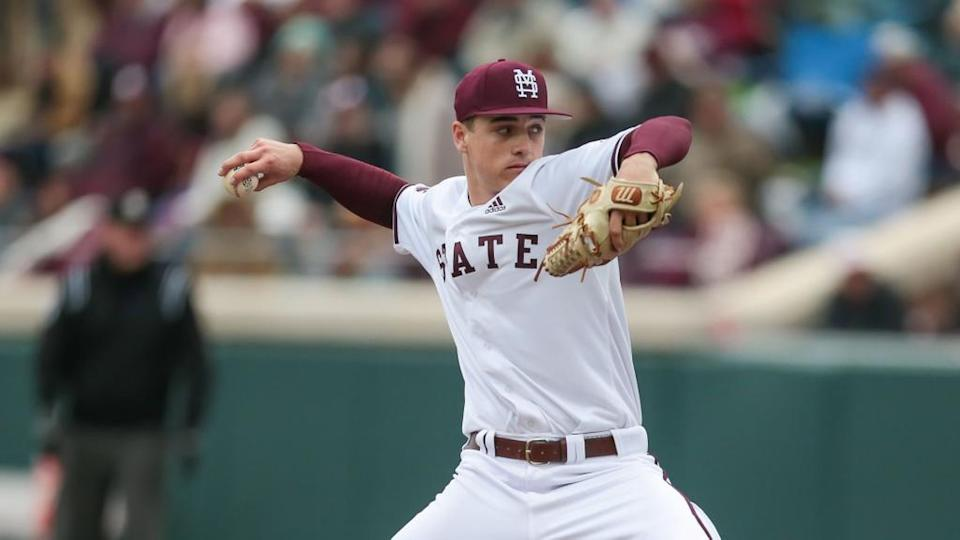 J.T. Ginn in white Miss State jersey throwing a pitch