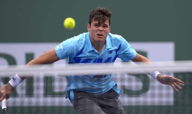 Milos Raonic, of Canada, returns a hit to Alexandr Dolgopolov, of Ukraine, during a quarterfinal match at the BNP Paribas Open tennis tournament on Thursday, March 13, 2014, in Indian Wells, Calif. (AP Photo/Mark J. Terrill)