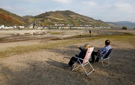 FILE PHOTO: A couple sit on their camping chairs amid the river bed of the dried out Rhine near Bacharach