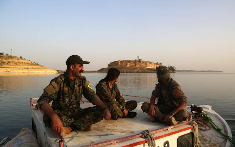 SDF fighters look towards Jaabar Castle as they sit on a boat at Lake Assad - Credit: AFP