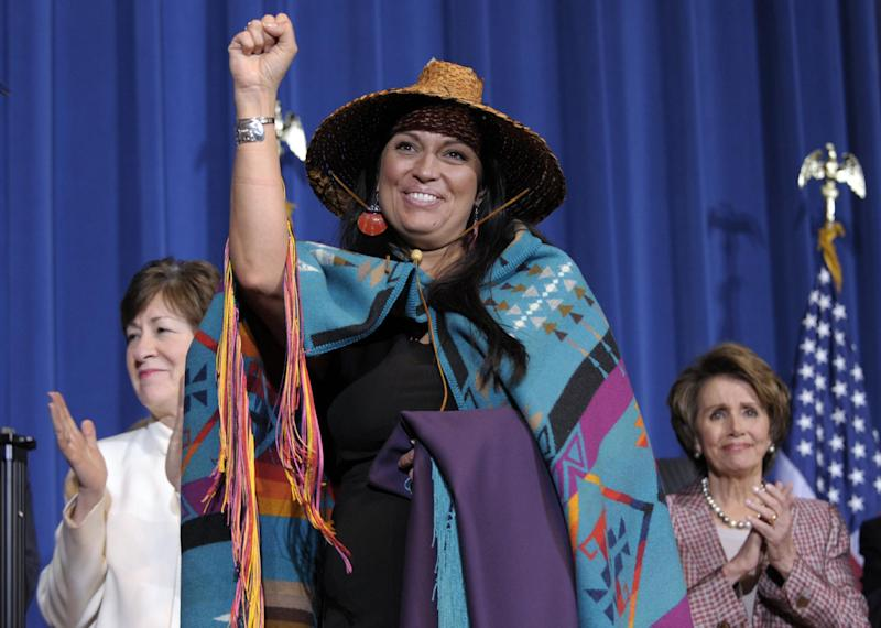 Deborah Parker, vice chairwoman of the Tulalip Tribes of Washington State, center, flanked by Sen. Susan Collins, R-Maine, left, and House Minority Leader Nancy Pelosi of Calif., gestures before President Barack Obama before he signed the Violence Against Women Act, Thursday, March 7, 2013, at the Interior Department in Washington. (AP Photo/Susan Walsh)