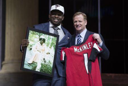 Apr 27, 2017; Philadelphia, PA, USA; Takkarist McKinley (UCLA) poses with NFL commissioner Roger Goodell as he holds a photo of his grandmother as he is selected as the number 26 overall pick to the Atlanta Falcons in the first round the 2017 NFL Draft at the Philadelphia Museum of Art.  Bill Streicher-USA TODAY Sports