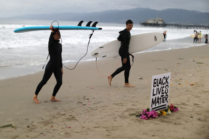 People step out of the ocean at The Black Girls Surf paddle-out in memory of George Floyd, who died in Minneapolis police custody, in Santa Monica