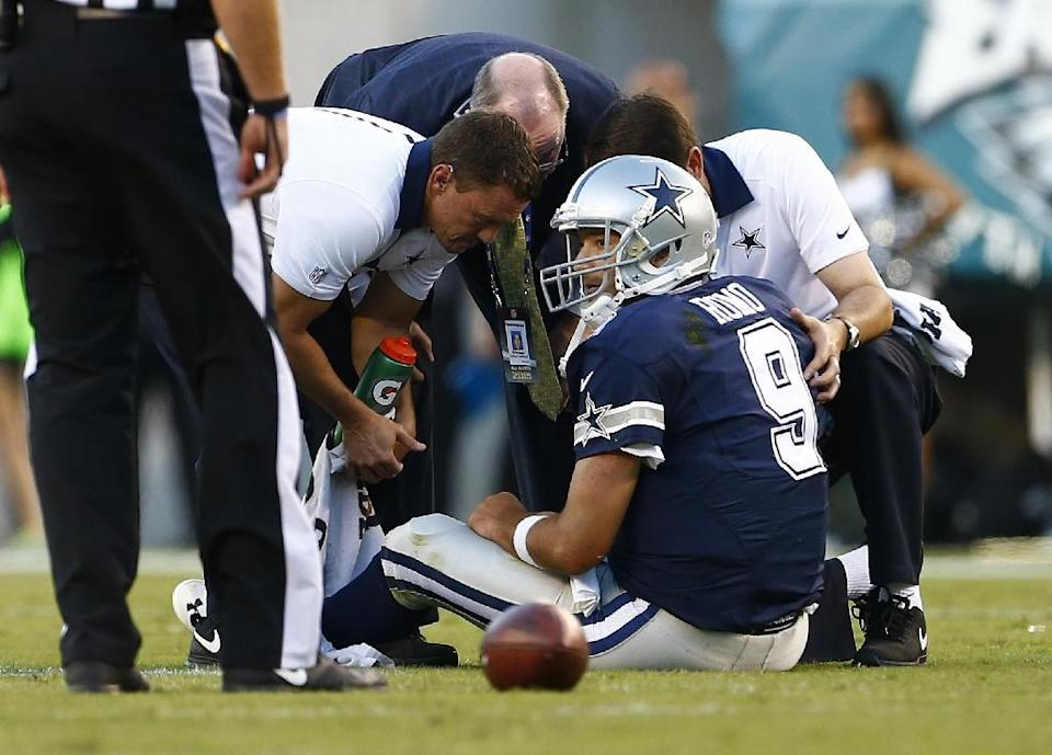 Dallas Cowboys quarterback Tony Romo is looked at by medical personal after getting injured during the game against the Philadelphia Eagles at Lincoln Financial Field on September 20, 2015 (AFP Photo/Rich Schultz)