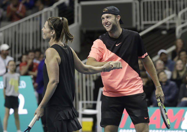 Savannah Guthrie, left, and partner Jack Sock celebrate during an exhibition tennis match against Roger Federer and Bill Gates in San Jose, Calif., Monday, March 5, 2018. (AP Photo/Jeff Chiu)