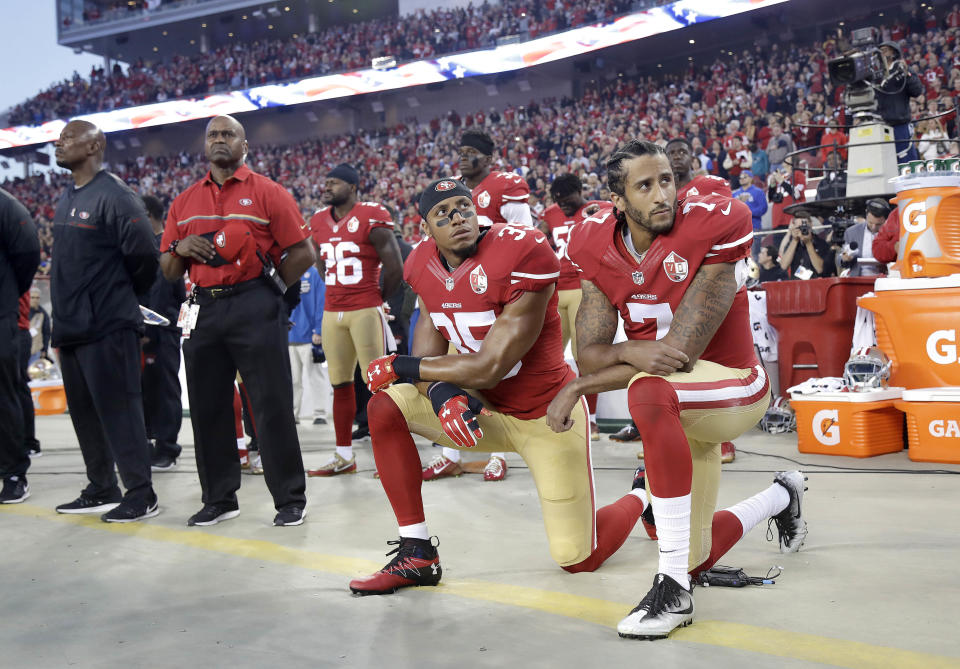 Eric Reid (35) and quarterback Colin Kaepernick (7) kneel during the national anthem before a game in 2016. (AP)