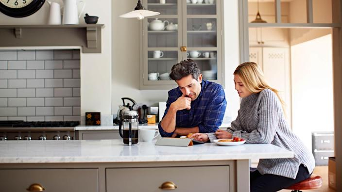 Shot of a young couple using a digital tablet while sitting at their kitchen table at home.