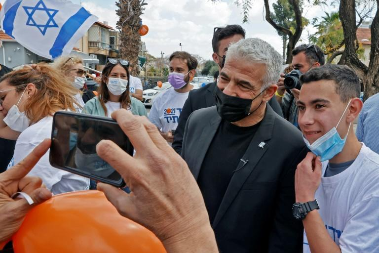 It was back to street politics in Israel for vote-seekers like opposition leader Yair Lapid (C)