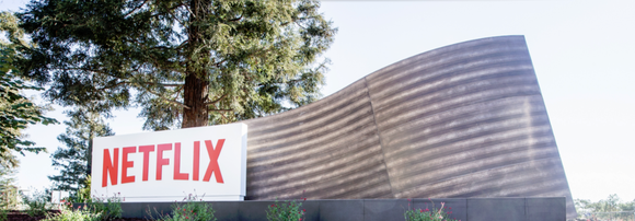 A Netflix sign on an exterior sculpture with trees as a backdrop.