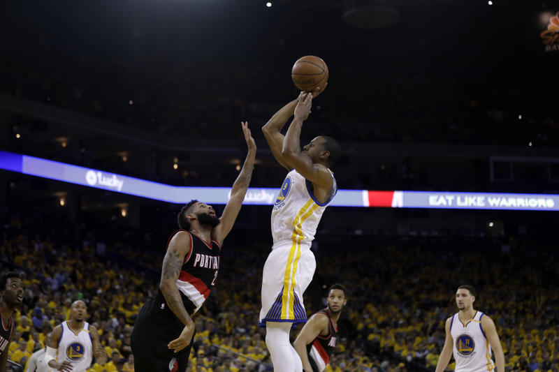 FILE - In this April 19, 2017, file photo, Golden State Warriors' Andre Iguodala, center, shoots over Portland Trail Blazers' Allen Crabbe during the first half in Game 2 of a first-round NBA basketball playoff series in Oakland, Calif. It is clear to Crabbe, and just about everyone else who is watching, that Portland's bench needs to do more against the Warriors in the first round of the NBA playoffs. (AP Photo/Marcio Jose Sanchez, File)