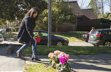 A woman places flowers near a building where three young Muslims were killed on Tuesday, in Chapel Hill, North Carolina February 11, 2015. REUTERS/Chris Keane