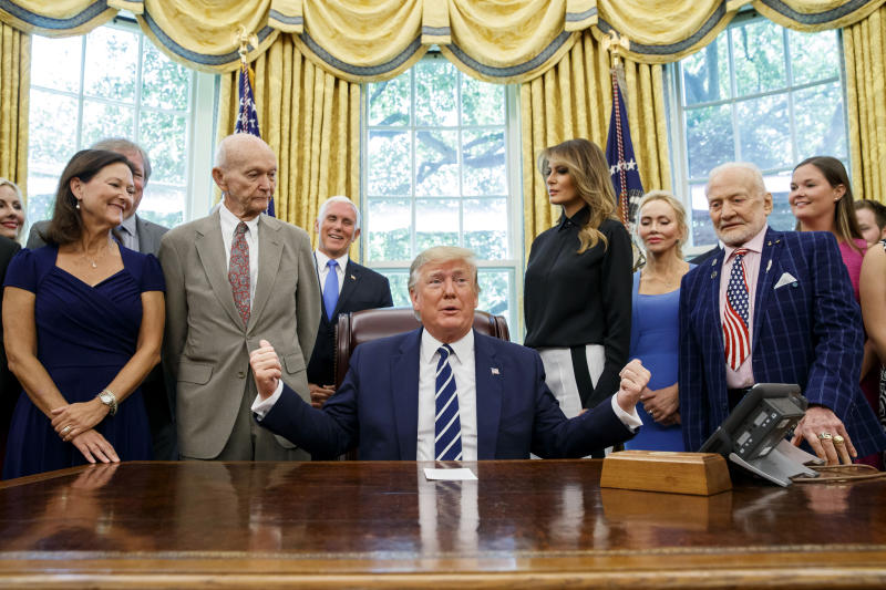 President Donald Trump, accompanied by Apollo 11 astronauts Michael Collins, second from left, and Buzz Aldrin, second from right, with Vice President Mike Pence and first lady Melania Trump, speaks during a photo opportunity commemorating the 50th anniversary of the Apollo 11 moon landing, in the Oval Office of the White House, Friday, July 19, 2019, in Washington. (AP Photo/Alex Brandon)