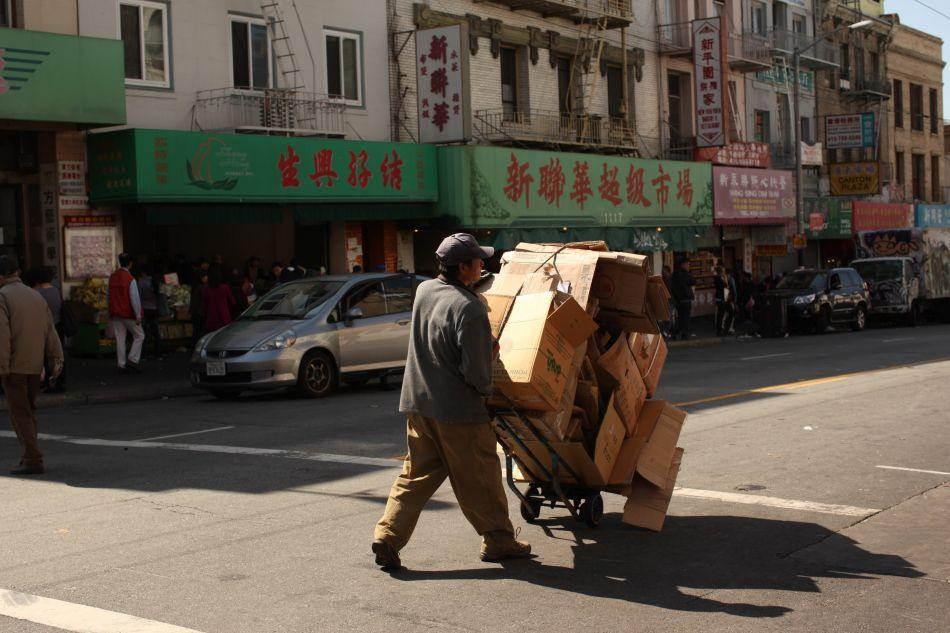 A man moves boxes in the Chinatown neighborhood in San Francisco, California.