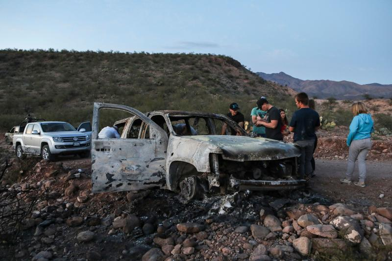Members of the Lebaron family watch the burned car where part of the nine murdered members of the family were killed and burned during an gunmen ambush on Bavispe, Sonora mountains, Mexico.