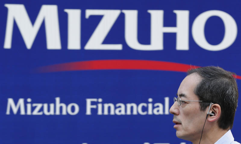 A man walk by a corporate sign of Mizuho Financial Group Inc. in Tokyo, Monday, Oct. 28, 2013. Japanese bank Mizuho Financial Group was lax in cleaning up loans that the lender discovered were linked to organized crime did not deliberately cover them up, an outside panel of lawyers said Monday. (AP Photo/Koji Sasahara)