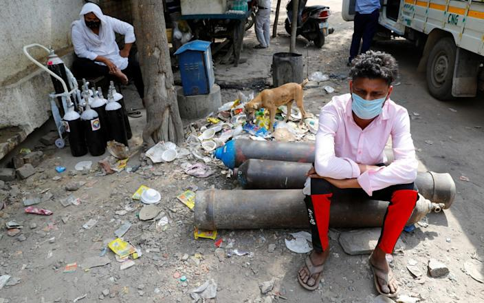 Sumit Kumar, 28, sits on an oxygen cylinder as he waits outside a factory in New Dehli to get it refilled - Reuters