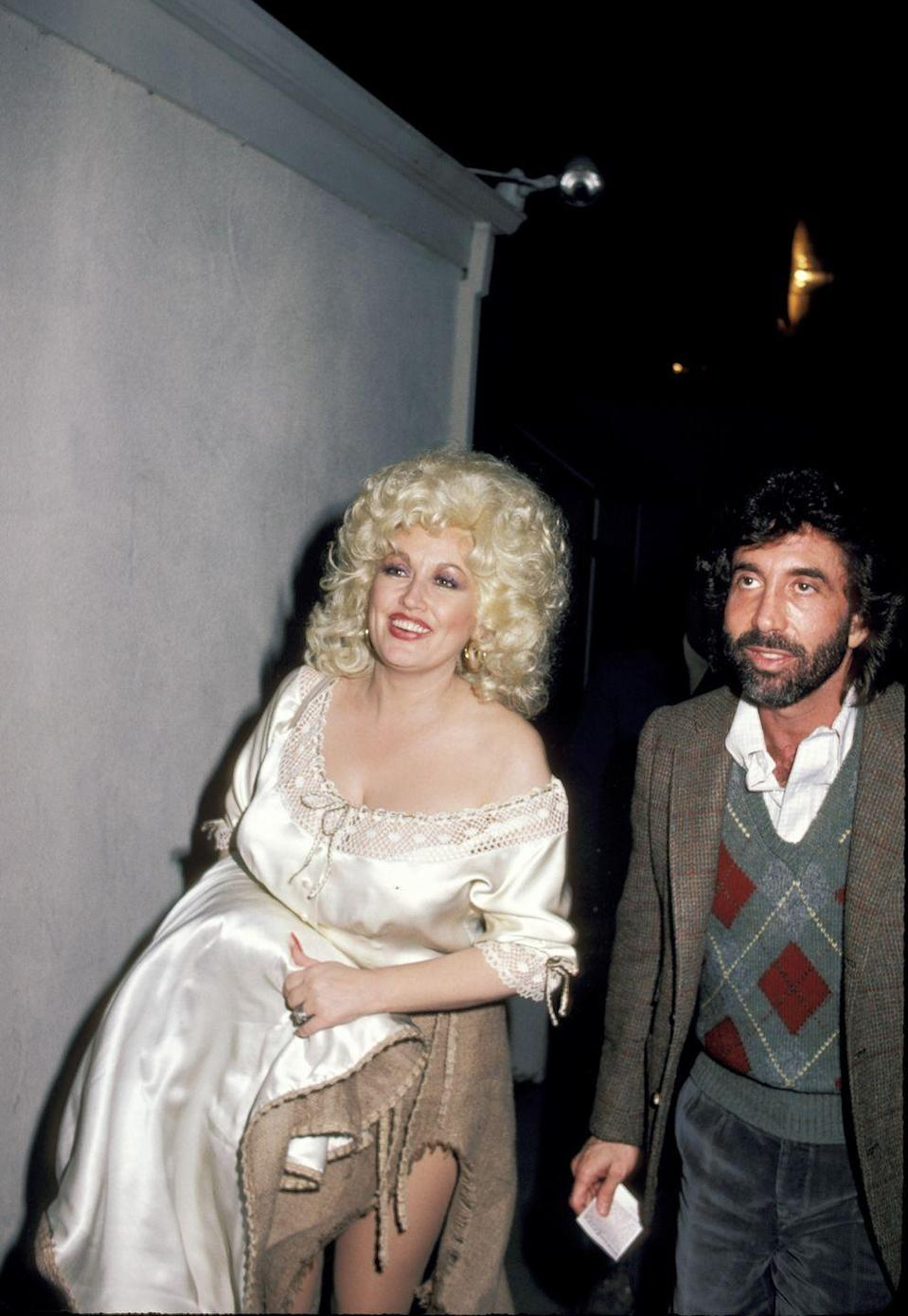 "<p>Dolly strolls with longtime manager and friend Sandy Gallin, who is credited with convincing her to record the 1977 smash hit ""Here You Come Again.""</p>"