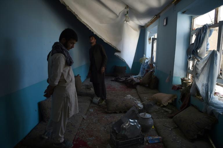 Afghan residents inspect inside a damage house following a hit by a NATO airstrike at a residential house in Kabul on September 28, 2017