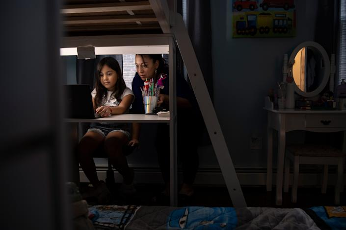 Luz Vanegas looks on as her daughter Dayna Bravo, 8, does school work at their home in North Bergen on Friday, November 13, 2020. Vanegas' life turned upside down this summer when her daughter, Estefania, gave birth to her first grandchild and suffered a heart attack during delivery leaving her in a coma. Vanegas not only worried about her daughter, but also began to take care of her new granddaughter, Emma, while her father works and they figure out what happened to Estafania. Meanwhile, Vanegas is also facing deportation.