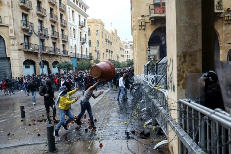 Anti-government protesters throw a large plant pot at Lebanese security forces in Beirut (AFP Photo/ANWAR AMRO)