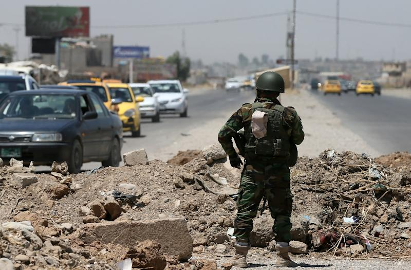 Security stands guard near a checkpoint held by IS militants on June 16, 2014 in Iraq's second city of Mosul