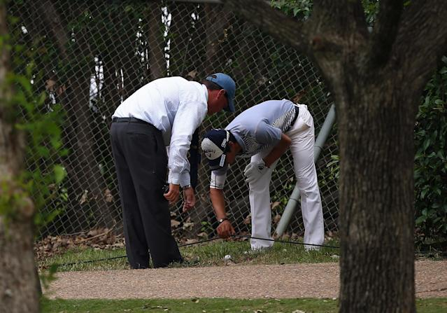 IRVING, TX - MAY 16: Ryo Ishikawa of Japan consults with a rules official while moving a cable near his ball during the first round of the 2013 HP Byron Nelson Championship at the TPC Four Seasons Resort on May 16, 2013 in Irving, Texas. (Photo by Tom Pennington/Getty Images)