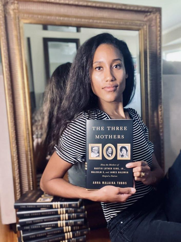 """Author Anna Malaika Tubbs poses with a copy of """"The Three Mothers."""" (via Twitter)"""