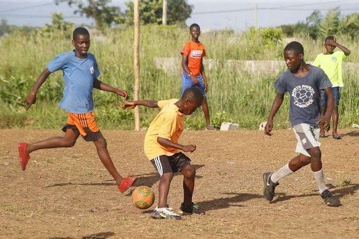 Liberian boys play soccer on a dusty pitch at Mount Barclay community, a suburb of Monrovia, Liberia, 25 September 2021.