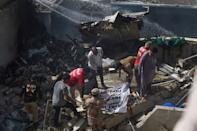 EDITORS NOTE: Graphic content / Rescue workers cover the body of a victim they recovered from the rubbles after a Pakistan International Airlines flight crashed in a residential neighbourhood in Karachi on May 22, 2020. - A Pakistan passenger plane with more than 100 people believed to be on board crashed in the southern city of Karachi on May 22, the country's aviation authority said. (Photo by Asif HASSAN / AFP) (Photo by ASIF HASSAN/AFP via Getty Images)