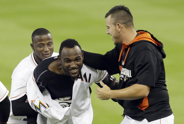 Miami Marlins' Marcell Ozuna, center, is congratulated by teammates Adeiny Hechavarria, left, and Jose Fernandez, right, after Ozuna hit a sacrifice fly driving in the game-wining run, 1-0, against the New York Mets in the ninth inning of a baseball game in Miami, Wednesday, May 7, 2014. Giancarlo Stanton scored the run. (AP Photo/Alan Diaz)