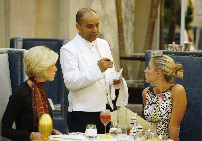 """Waiter Sayed Islam speaks with Ruland and Parker in """"The Plaza"""" hotel's """"Palm Court"""" the first day that the hotel re-opened following extensive renovations in New York"""