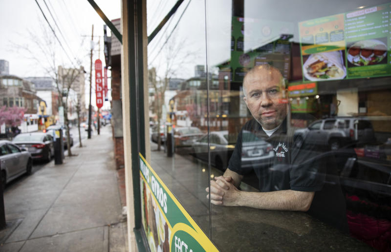 "Paul Boutros, owner of East Side Pockets, a small restaurant near Brown University, looks out onto an empty street since students were sent home two weeks ago, Wednesday, March 25, 2020, in Providence, R.I. ""He's not being realistic. How can you open if the cases are climbing day after day?"" asked Boutros on Trump's call to restart the economy by mid-April. ""You go to Walmart, you don't know if the people around you, if they have the virus. People come to our restaurant. I don't know if they have the virus."" (AP Photo/David Goldman)"