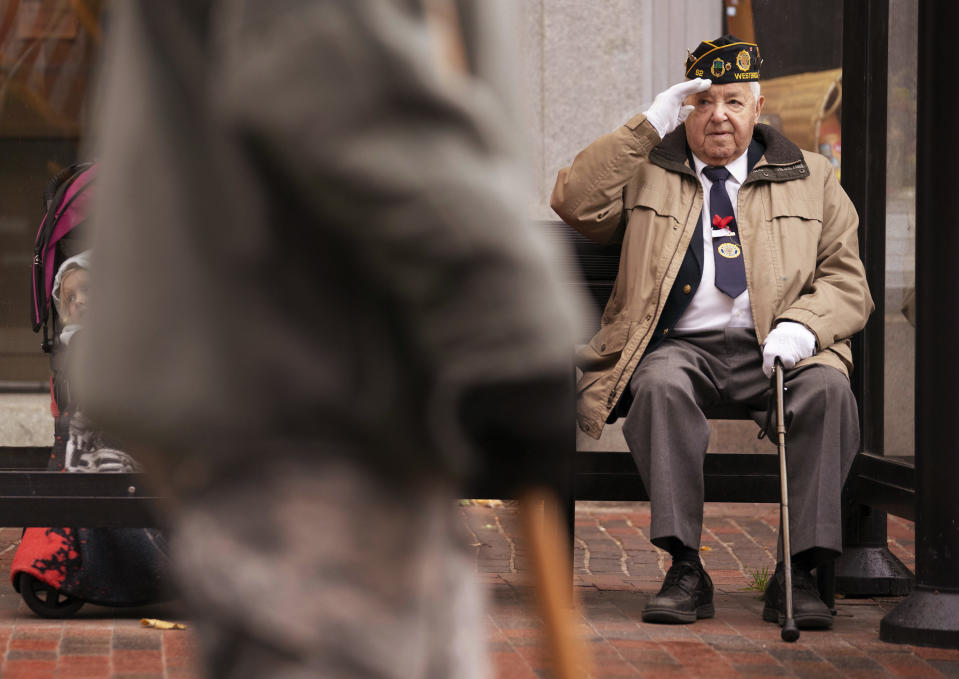 PORTLAND, ME - NOVEMBER 11: Tom Caron of Portland salutes soldiers walking along Congress Street during Portlands Veterans Day parade on Monday, November 11, 2019. Caron served in the U.S. Army in the 1950s and said he has participated in Portlands Veterans Day parade in the past but was showing his support for marchers this year from a covered a bus stop bench on Monday. (Staff Photo by Gregory Rec/Portland Press Herald via Getty Images)