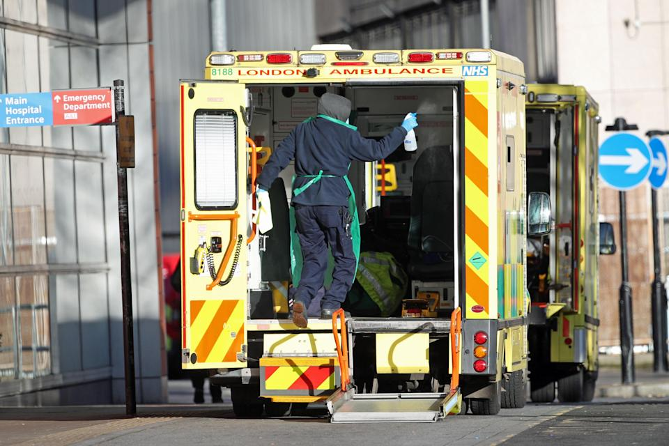 A worker in PPE cleans the back of an ambulance after dropping off a patient at the Royal London Hospital during the second wave of coronavirus (Yui Mok/PA) (PA Archive)