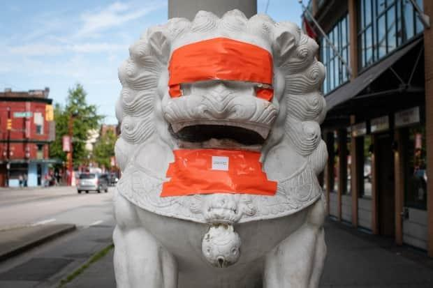 The lion statues of Vancouver's Chinatown Millennium Gate are seen covered in orange tape on May 29, 2020, after they were defaced for the second time in a matter of weeks.