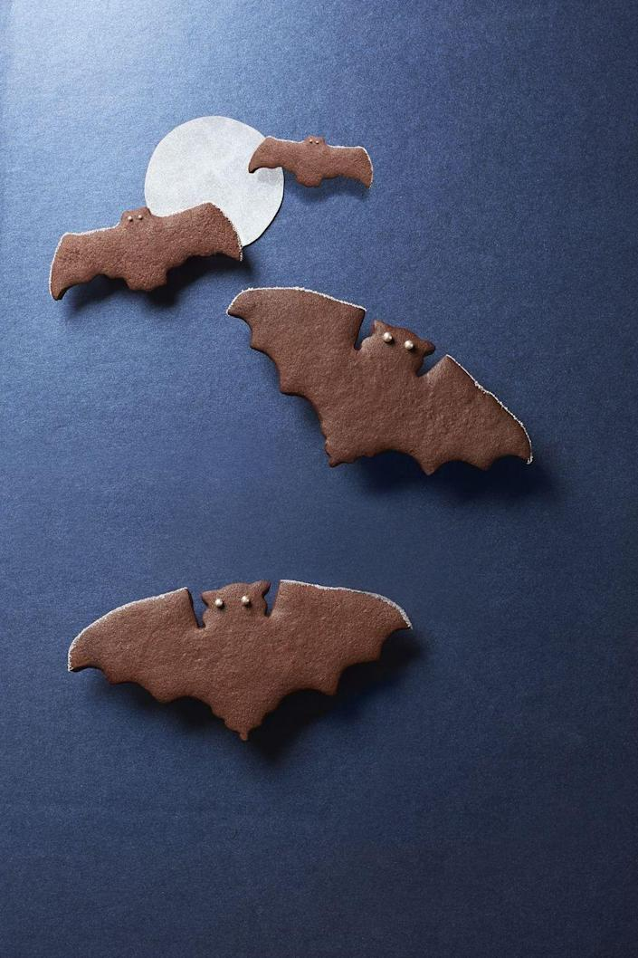 """<p>These spiced chocolate bat cookies are decorated with silver edible sugar pearls. </p><p><strong><em><a href=""""https://www.womansday.com/food-recipes/food-drinks/recipes/a40295/spiced-chocolate-bat-cookies-recipe-clx1014/"""" rel=""""nofollow noopener"""" target=""""_blank"""" data-ylk=""""slk:Get the Spiced Chocolate Bat Cookies recipe."""" class=""""link rapid-noclick-resp"""">Get the Spiced Chocolate Bat Cookies recipe. </a></em></strong> </p>"""