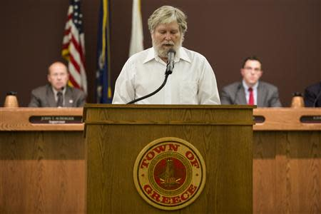 Tom Lynch delivers a Baha'i prayer before the start of a town board meeting at the Greece Town Hall in Greece, New York