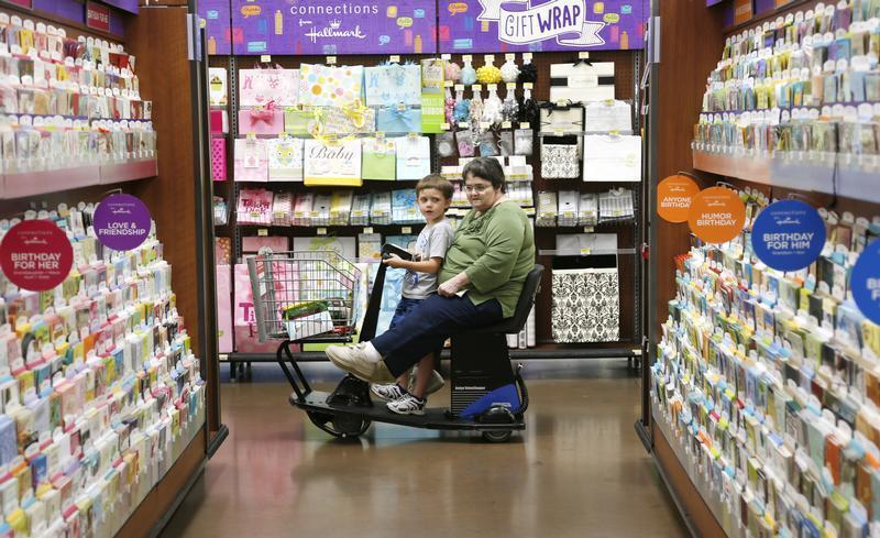 A woman riding an electric cart shops with a child at a Walmart Supercenter in Rogers