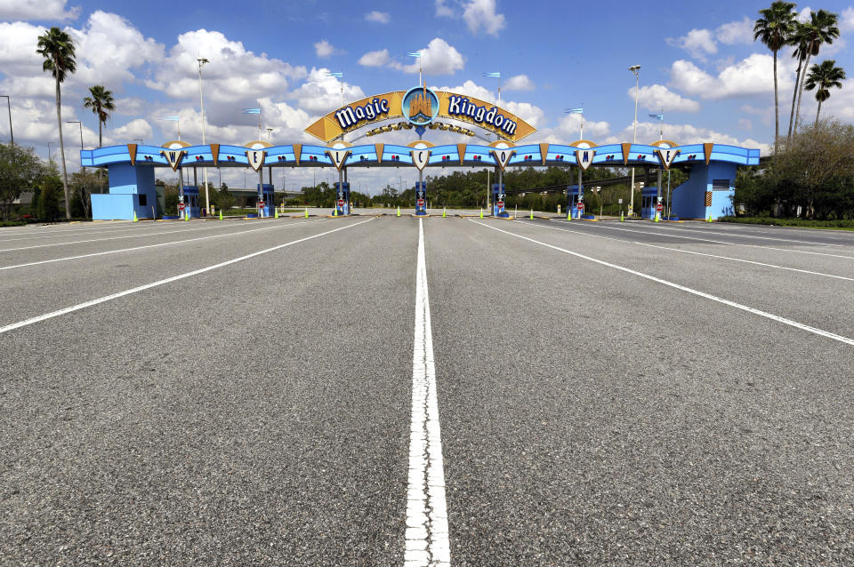 FILE - In this March 24, 2020, file photo, lanes leading to the parking plaza entrance of Walt Disney World's Magic Kingdom sit empty during its second week of closure in response to the coronavirus pandemic in Orlando. From Cape Cod to California, festivals are being canceled, businesses in tourist havens are looking at empty reservation books, and people who have been cooped up through a dismal spring are worrying summer will bring just more of the same. (Joe Burbank/Orlando Sentinel via AP, File)