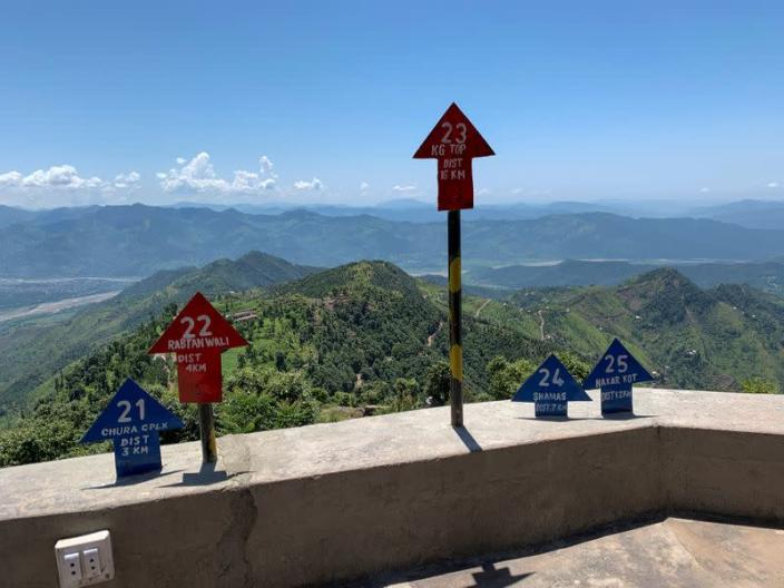 Signs displaying area distance are seen at a hilltop post during a trip organised by the army, near the Line of Control (LoC), in Charikot Sector, Kashmir