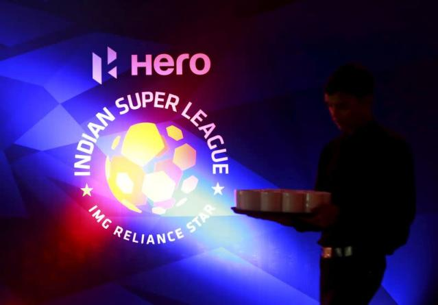FILE PHOTO: A waiter walks past a logo of Indian Super League before a news conference during the domestic player auction and draft in Mumbai