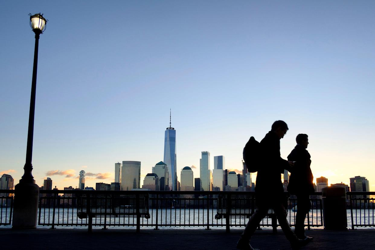 Early morning commuters on the New Jersey side of the Hudson River walk to work past the New York City skyline, Tuesday, Dec. 18, 2018, in Jersey City, N.J. (AP Photo/J. David Ake)