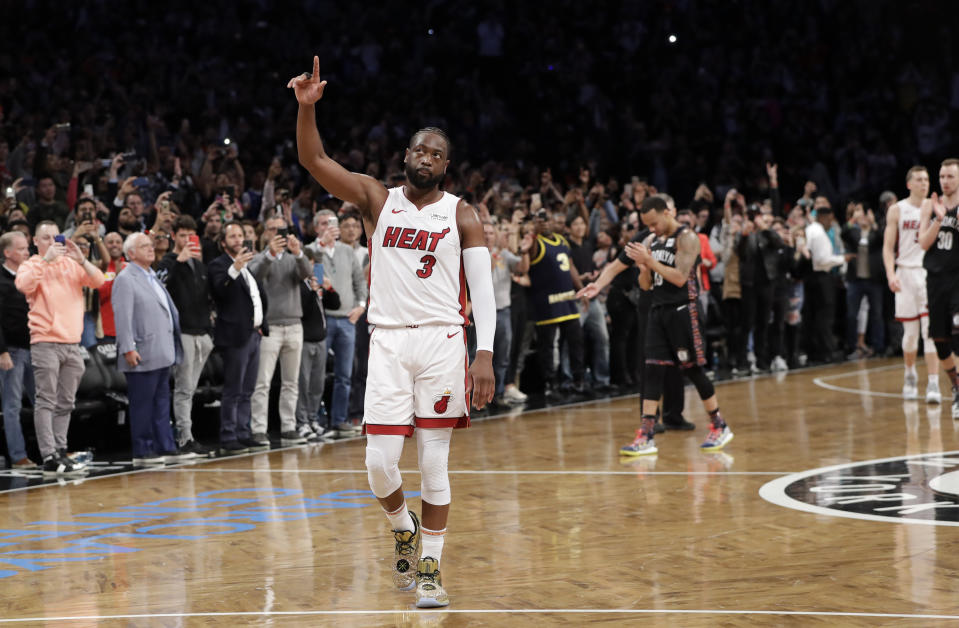 Miami Heat guard Dwyane Wade (3) acknowledges the crowd's cheers after playing in the final NBA basketball game of his career, against the Brooklyn Nets on Wednesday, April 10, 2019, in New York. (AP Photo/Kathy Willens)
