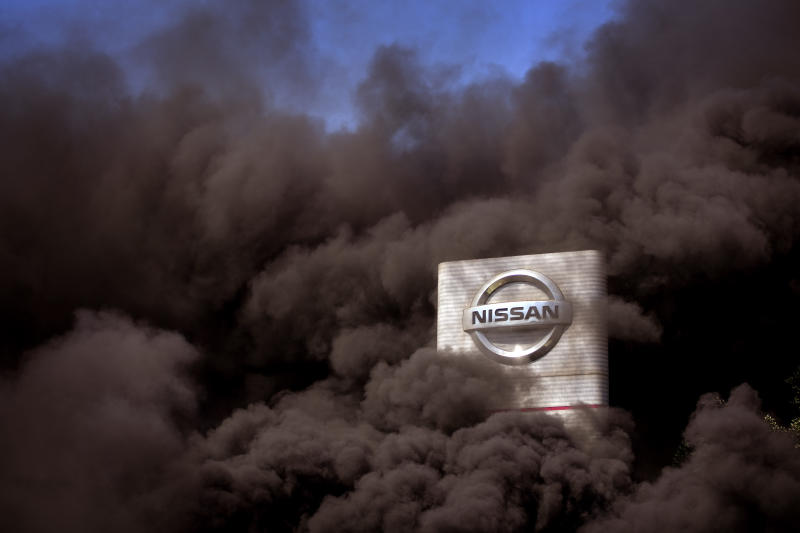 Smoke rises over the Nissan factory as workers burn tires during a protest in Barcelona, Spain, Thursday, May 28, 2020. Japanese carmaker Nissan Motor Co. has decided to close its manufacturing plans in the northeastern Catalonia region, resulting in the loss of some 3,000 direct jobs. (AP Photo/Emilio Morenatti)